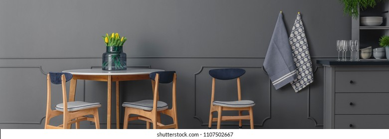 Grey, wooden chairs at round table against grey wall with molding in dining room interior