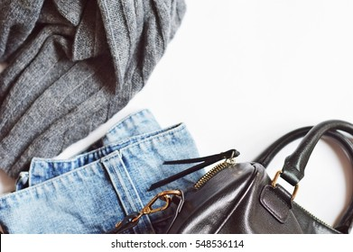 Grey woolen knitted sweater, blue denim skirt, and a female handbag. Trendy fashion blogger outfit. Autumn or winter women's clothing. Flat lay photo, top view