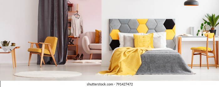 Grey and yellow bedding on bed with bedhead in bright bedroom interior with wardrobe and yellow vintage armchair