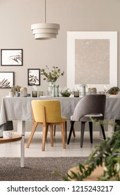 Grey and yellow chair at table under lamp in dining room interior with posters and plants. Real photo