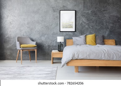Grey and yellow room with king-size bed, poster and lamp standing on bedside table