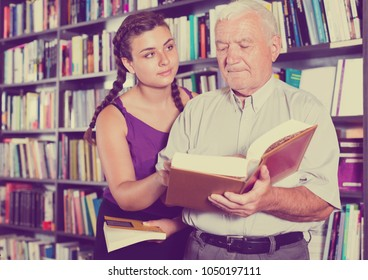 greybeard with girl are reading books in bookstore.