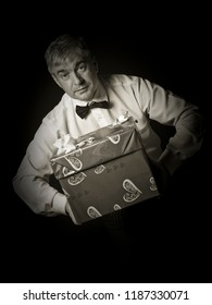 A grey-hair red imposing respectable man with gifts. A handsome imposing respectable grey-hair ed man giving presents in red wrapping paperagainst a black background.