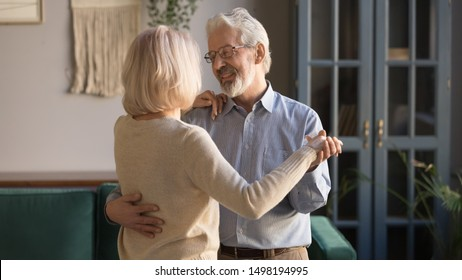 Grey-hair senior husband and wife embrace enjoy romantic date at home dancing together in living room, smiling elderly couple spend weekend tender time waltzing celebrating wedding anniversary