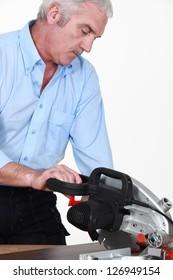 Grey-haired carpenter sawing laminate flooring