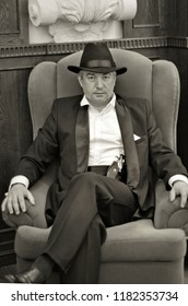 A grey-haired elderly mobster in an interior... A grey-hair elderly mobster with a gun wearing a black suit and a hat is sitting in an armchair in an old interior in retro-style.