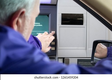 Grey-haired man at drive-up ATM machine leaning out car window and pushing button - Instructions in English and Spanish - Selective focus.