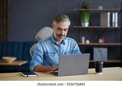 Grauhaariger Senior Mann, der im Heimbüro mit Laptop arbeitet. Geschäftsporträt von gut aussehenden Managern am Arbeitsplatz. Lernen Sie Online-, Online-Kurse. Geschäftskonzept.
