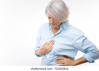 Grey-haired woman suffering from stomachache