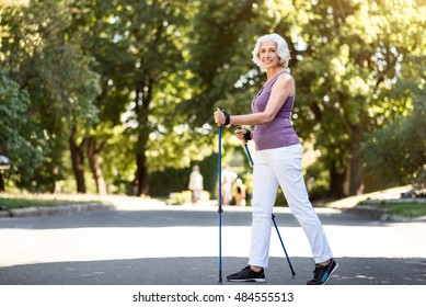 Grey-haired woman walking with tracking sticks in the park