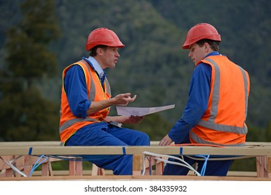 GREYMOUTH, NEW ZEALAND, DECEMBER 21, 2014:Two unidentified electricians discuss the plan for a major construction job near Greymouth, New Zealand, 21,12,2014