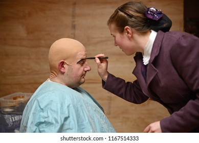 GREYMOUTH, NEW ZEALAND, JULY 20, 2018: An actress in period costume doubles as a makeup artist and prepares a colleague in his bald cap for a stage performance.