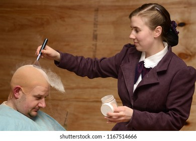GREYMOUTH, NEW ZEALAND, JULY 20, 2018: The powder flies as an actress in period costume doubles as a makeup artist and prepares a colleague in his bald cap for a stage performance.