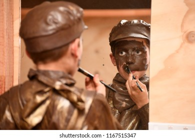 GREYMOUTH, NEW ZEALAND, JULY 20, 2018: A boy works as his own makeup artist and paints his face in preparation for a stage performance.