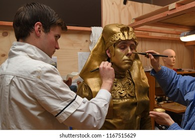 GREYMOUTH, NEW ZEALAND, JULY 23, 2018: Make-up artists prepare an actor for his role as an egyptian statue in a stage production