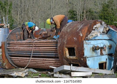 GREYMOUTH, NEW ZEALAND, MAY 14, 2018: An unidentified engineer cuts up an old boiler for scrap metal