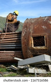 GREYMOUTH, NEW ZEALAND, MAY 14, 2018: An engineer cuts up an old boiler for scrap metal