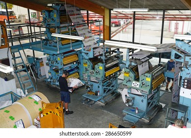 GREYMOUTH, NEW ZEALAND, MAY 22, 2015:  An unidentified printer checks the quality of his workmanship while printing a newspaper on May 22, 2015 in Greymouth, New Zealand.