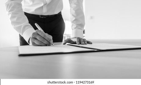 Greyscale image of businessman standing at his desk signing contract or legal document.
