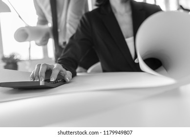 Greyscale image of businesswoman working on calculator as her partner stands behind her in a low angle view.