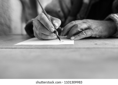 Greyscale image of an elderly man doing calligraphy writing using a nib pen and ink on a sheet of white paper in a low angle close up view of his hands with foreground copy space.