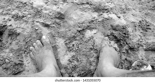 a greyscale photo illustrating sand dip of man's legs