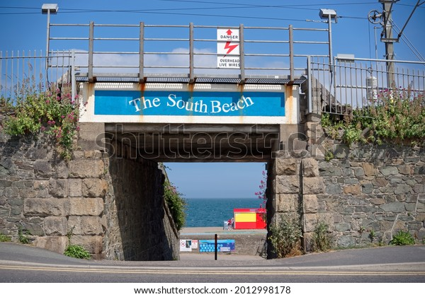 GREYSTONES, CO. WICKLOW, IRELAND - JULY 2, 2021: Railway bridge with an entrance to the South Beach in Greystones town on sunny summer day.