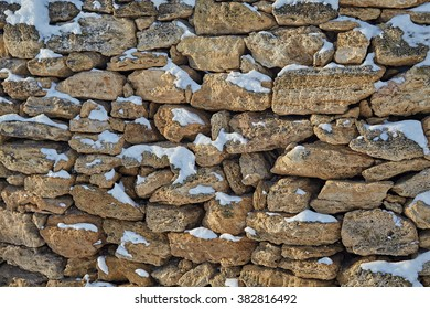Grey-yellow stones in snow. A wall. Abstract. Structures. A background. Winter