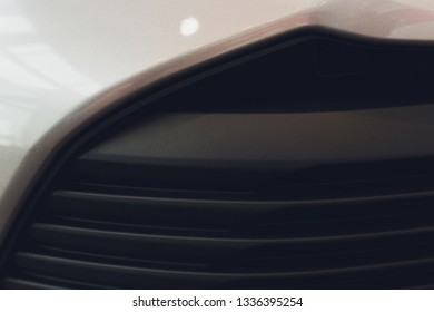 Grid of car with sunflare. Radiator grille. Metal close-up texture background. Chrome grill of big powerful engine macro.