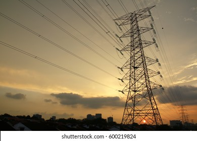 Grid electricity transmission tower with sunset sky