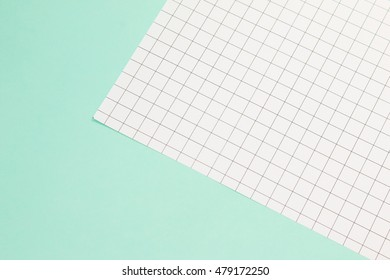 Grid pattern paper on soft green background.