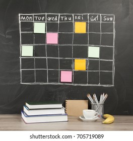 Grid timetable schedule with note paper on black chalkboard background