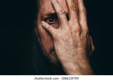 Grieving man after receiving shocking or bad news, with hand on face and a tear in his eye - grief concept.