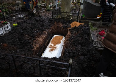 Grieving relatives bury a white coffin in a pit, throwing the coffin to the ground