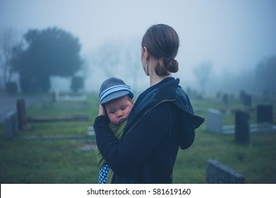 A grieving young mother is standing with her baby by a tombstone in a graveyard