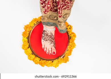 Griha Pravesh Concept - Rright feet of a Newly married Indian Hindu bride in Saree stepping in a plate filled with liquid kumkum tbefore entering house for the first time