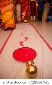 Griha Pravesh Ritual - Right feet of a Newly married Indian Hindu bride in Saree stepping in a plate filled with liquid kumkum before entering house for the first time. Bengali wedding rituals.