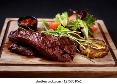 grill and barbeque, meat restaurant menu, juicy medium rare skirt steak served with vegetable salad and potatoes on board, traditional american cuisine