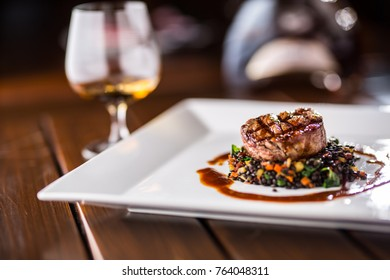 Grill beef steak black lentils mixed with vegetable and cognac or brandy as drink.