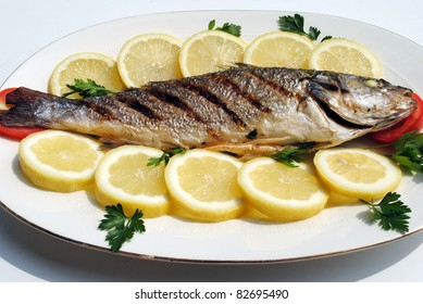 grill cooked fish with lemon slices and parsley