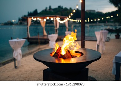 Grill with flames inside. Round table-cooking surface. On the beach, in the background of the gazebo by the water with garlands, in the twilight light.