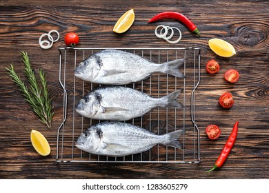 Grill with fresh dorado fish and ingredients on wooden background
