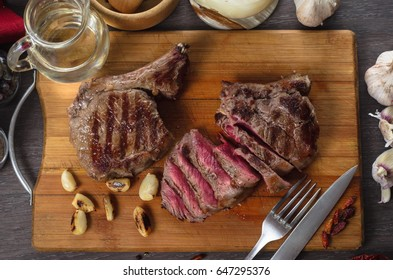 Grill meat rib eye steak composition on wooden background