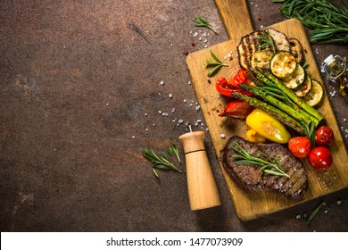 Grill menu. Beef steak grilled with vegetables on cutting board at dark background. Barbecue dish. Top view with copy space.