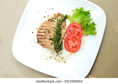 Grill pork with black pepper and decorated with various vegetable on white plate.