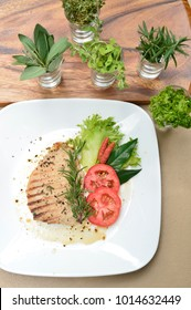 Grill pork with black pepper and decorated with tomato slice,lettuce leaf and place rosemary leaf on white dish.