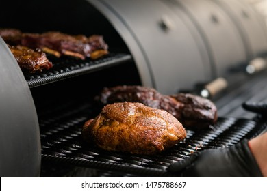 Grill restaurant kitchen. Chef cooking poultry, beef and pork meat, ribs in BBQ smoker.