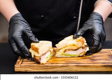 Grill restaurant menu. Closeup of chef hands serving smoked turkey breast sandwich on wooden board.