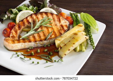 Grill Salmon with Teriyaki sauce and fresh pepper with rosemary in white dish on brown table
