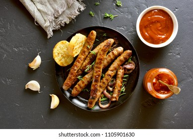 Grill sausage with tomato sauce over black stone background. Top view, flat lay
